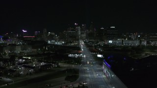 DX0002_193_026 - 5.7K stock footage aerial video flying by Grand River Avenue, focus on skyline at night, Downtown Detroit, Michigan