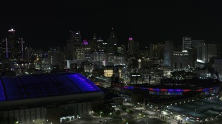 DX0002_193_044 - 5.7K stock footage aerial video view of skyline from Comerica Park, reveal Ford Field at night, Downtown Detroit, Michigan