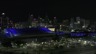 DX0002_193_045 - 5.7K stock footage aerial video ascend past stadiums for view of skyline at night, Downtown Detroit, Michigan