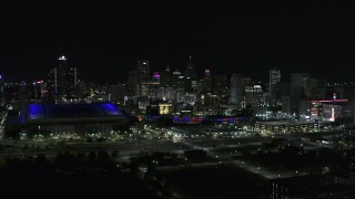 DX0002_193_047 - 5.7K stock footage aerial video the skyline behind Ford Field and Comerica Park stadiums at night, Downtown Detroit, Michigan
