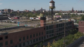 DX0002_194_047 - 5.7K stock footage aerial video of orbiting an abandoned brick building with water tower in Detroit, Michigan
