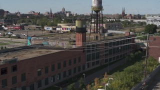 DX0002_194_049 - 5.7K stock footage aerial video of orbiting an abandoned brick building with a water tower on the roof in Detroit, Michigan