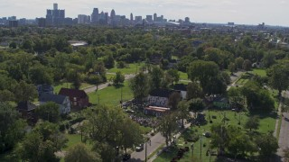 DX0002_195_009 - 5.7K stock footage aerial video of circling the Heidelberg Project outdoor art display and urban homes, reveal the skyline in Detroit, Michigan