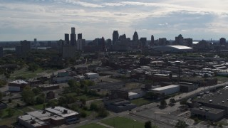 DX0002_195_021 - 5.7K stock footage aerial video of flying by the city's skyline, seen from brick industrial buildings, Downtown Detroit, Michigan