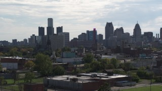 DX0002_195_024 - 5.7K stock footage aerial video focus on the city's skyline while descending near brick buildings, Downtown Detroit, Michigan