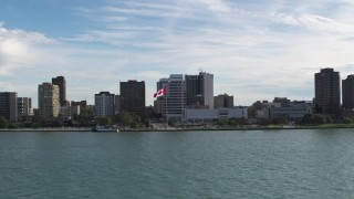 DX0002_196_005 - 5.7K stock footage aerial video of approaching office buildings and Canadian flag by the river in Windsor, Ontario, Canada