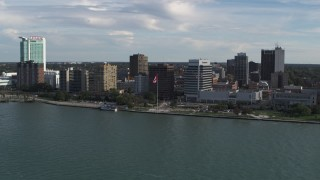 DX0002_196_007 - 5.7K stock footage aerial video of orbiting office buildings and Canadian flag by the river in Windsor, Ontario, Canada