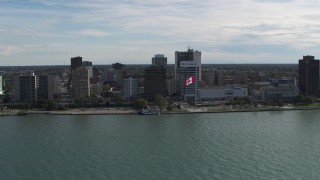 DX0002_196_008 - 5.7K stock footage aerial video orbit riverfront office buildings and Canadian flag in Windsor, Ontario, Canada