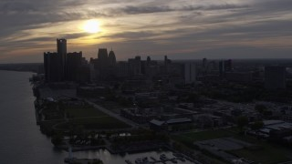 DX0002_197_004 - 5.7K stock footage aerial video ascend and flyby the setting sun behind clouds above the Downtown Detroit skyline, Michigan