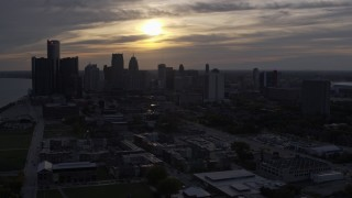 DX0002_197_005 - 5.7K stock footage aerial video flyby the setting sun behind clouds above the Downtown Detroit skyline, Michigan