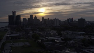 DX0002_197_006 - 5.7K stock footage aerial video of flying by the city's skyline with the setting sun in the clouds above, Downtown Detroit, Michigan