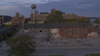 DX0002_197_015 - 5.7K stock footage aerial video ascend by abandoned factory building and water tower at sunset, Detroit, Michigan