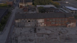 DX0002_197_016 - 5.7K stock footage aerial video descend by abandoned factory building at sunset, Detroit, Michigan