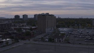 DX0002_197_024 - 5.7K stock footage aerial video focus on an apartment building during descent at sunset, Detroit, Michigan