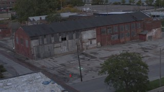 DX0002_197_050 - 5.7K stock footage aerial video orbit an abandoned brick building at sunset, Detroit, Michigan