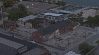 DX0002_197_052 - 5.7K stock footage aerial video flying away from an abandoned brick building at sunset, Detroit, Michigan
