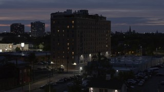 DX0002_198_024 - 5.7K stock footage aerial video descend and circle an apartment building at twilight, Detroit, Michigan