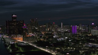 DX0002_198_035 - 5.7K stock footage aerial video flyby the brightly lit city skyline at night, Downtown Detroit, Michigan
