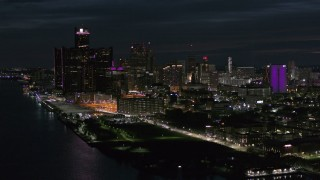 DX0002_198_037 - 5.7K stock footage aerial video of the brightly lit skyscrapers in the city skyline at night, Downtown Detroit, Michigan