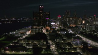 DX0002_198_039 - 5.7K stock footage aerial video GM Renaissance Center and brightly lit skyscrapers at night, Downtown Detroit, Michigan