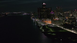 DX0002_198_043 - 5.7K stock footage aerial video of orbiting GM Renaissance Center seen from river at night, Downtown Detroit, Michigan