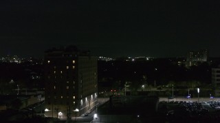 DX0002_198_060 - 5.7K stock footage aerial video orbit an apartment building at nighttime, Detroit, Michigan