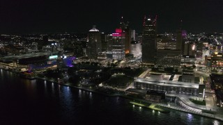 DX0002_199_005 - 5.7K stock footage aerial video stationary view of towering skyscrapers and Hart Plaza at night, Downtown Detroit, Michigan