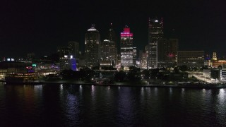 DX0002_199_013 - 5.7K stock footage aerial video focus on Hart Plaza and towering skyscrapers at night while descending by river, Downtown Detroit, Michigan