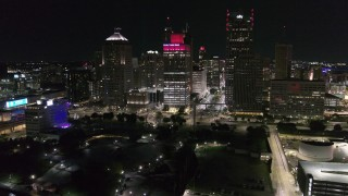 DX0002_199_016 - 5.7K stock footage aerial video a reverse view of Hart Plaza and towering skyscrapers at night, Downtown Detroit, Michigan