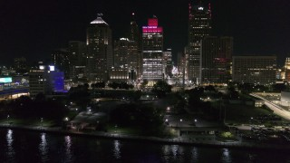 DX0002_199_023 - 5.7K stock footage aerial video orbit Hart Plaza, focus on tall skyscrapers at night, Downtown Detroit, Michigan