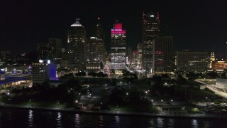 DX0002_199_026 - 5.7K stock footage aerial video ascend by riverfront Hart Plaza, focus on tall skyscrapers at night, Downtown Detroit, Michigan