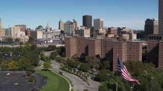 DX0002_200_006 - 5.7K stock footage aerial video descend by apartment buildings with view of skyline, Downtown Buffalo, New York