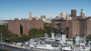 DX0002_200_015 - 5.7K stock footage aerial video ascend past apartment buildings and warship to focus on skyline, Downtown Buffalo, New York