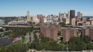 DX0002_200_016 - 5.7K stock footage aerial video focus on skyline and descend past apartment buildings, Downtown Buffalo, New York
