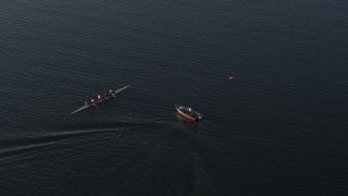DX0002_203_035 - GLITCH 5.7K stock footage aerial video ascend and approach a rowboat and speedboat at sunset, Buffalo, New York