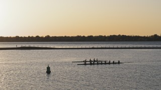 DX0002_203_045 - 5.7K stock footage aerial video of orbiting rowboats on Lake Erie at sunset, Buffalo, New York