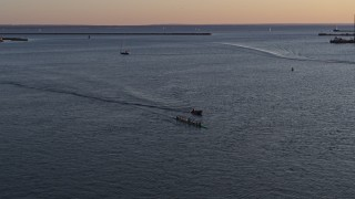 DX0002_204_007 - 5.7K stock footage aerial video of rowboat and speedboat on Lake Erie at sunset, Buffalo, New York
