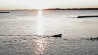 DX0002_204_013 - 5.7K stock footage aerial video of a stationary view of Lake Erie as a rowboat and speedboat pass at sunset, Buffalo, New York