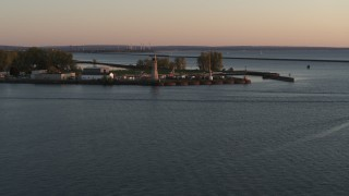 DX0002_204_019 - 5.7K stock footage aerial video ascend away from Lake Erie lighthouse at sunset, Buffalo, New York
