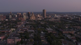 DX0002_204_037 - 5.7K stock footage aerial video of Seneca One Tower and skyline seen while descending past homes at twilight, Downtown Buffalo, New York