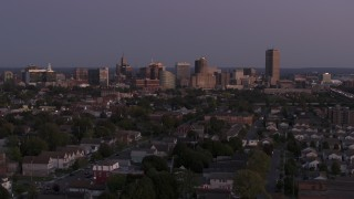 DX0002_204_038 - 5.7K stock footage aerial video of the skyline seen while flying past homes at twilight, Downtown Buffalo, New York
