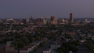 DX0002_204_040 - 5.7K stock footage aerial video of the skyline seen while ascending past apartments and homes at twilight, Downtown Buffalo, New York