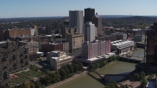 DX0002_206_004 - 5.7K stock footage aerial video orbiting riverfront hotels and the city's skyline, Downtown Rochester, New York