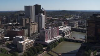 DX0002_206_006 - 5.7K stock footage aerial video ascend over river for view of hotel near the city's skyline, Downtown Rochester, New York