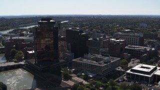 DX0002_206_014 - 5.7K stock footage aerial video descend with view of office buildings and hotel by the Genessee River, Downtown Rochester, New York