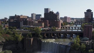 DX0002_206_032 - 5.7K stock footage aerial video fly over falls and bridges to toward the city's skyline, Downtown Rochester, New York