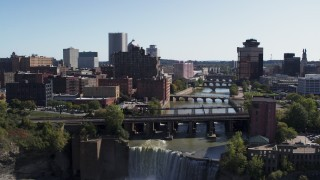 DX0002_207_003 - 5.7K stock footage aerial video ascend over falls for view of river bridges and skyline Downtown Rochester, New York