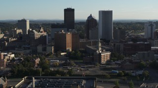 DX0002_209_002 - 5.7K stock footage aerial video ascend and orbit apartment building near high-rises, Downtown Rochester, New York