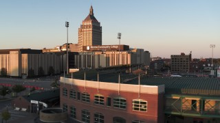 DX0002_209_035 - 5.7K stock footage aerial video fly over Frontier Field toward college and Kodak Tower at sunset, Rochester, New York