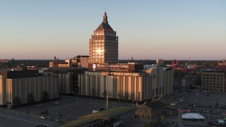 DX0002_209_040 - 5.7K stock footage aerial video descend away from Kodak Tower and a college at sunset, Rochester, New York